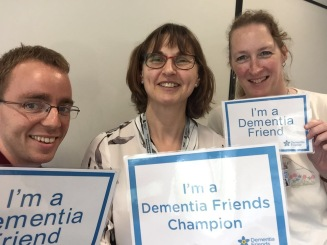 2 women and 1 man holding signs saying I'm a Dementia Friends Champion